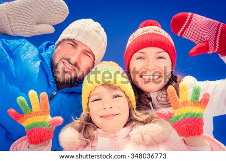 Happy family having fun outdoors in winter against blue sky background. Low angle view - stock photo