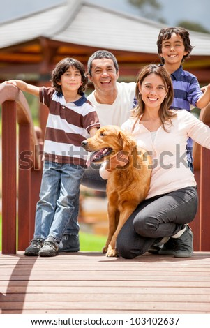 Happy family having fun outdoors with their dog - stock photo