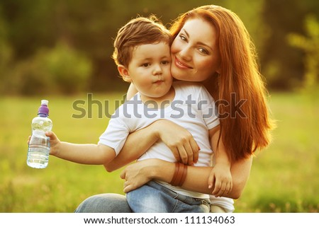 happy family having fun. son holding a bottle of water and mother holding him in her arms. outdoor shot. - stock photo