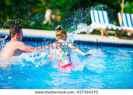 Happy family having fun together in outdoors swimming pool - stock photo