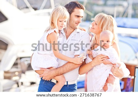 Happy family having fun walking on the mooring near yachts - stock photo