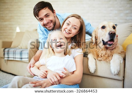 Happy family having home rest with their pet - stock photo