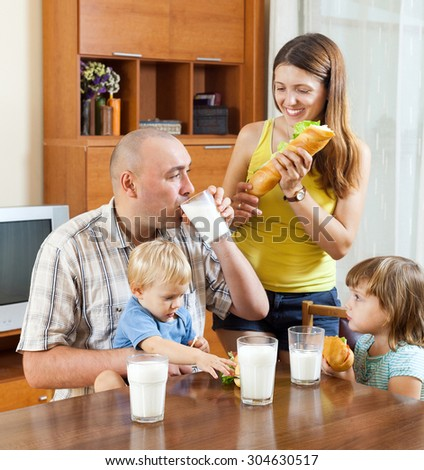 happy family   having lunch with sandwiches at home together - stock photo