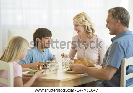 Happy family having meal together at dining table - stock photo