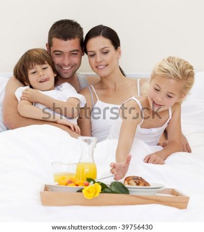 Happy family having nutritive breakfast in bedroom - stock photo