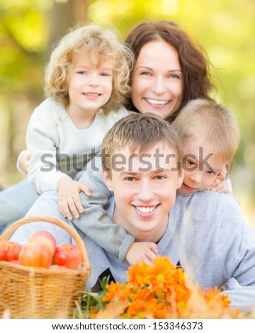 Happy family having picnic outdoors in autumn park against blurred leaves background - stock photo