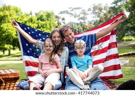 Happy family holding american flag in the park on a sunny day - stock photo