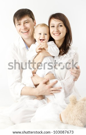 Happy family holding smiling baby over white background - stock photo