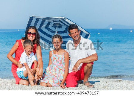 Happy family holidaying on a sandy beach - stock photo
