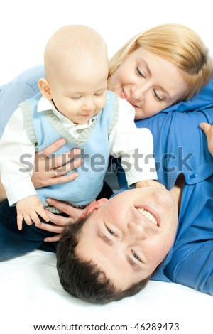 happy family home: father, mother and baby lying down and smiling - stock photo