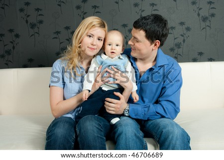 happy family home: father, mother and baby sitting on the sofa - stock photo