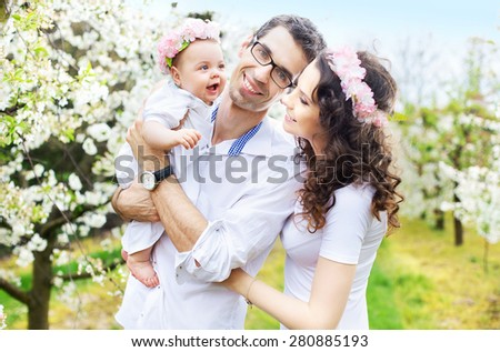 Happy family in a blossom garden - stock photo
