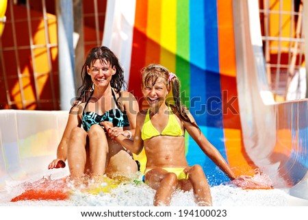 Happy family  in bikini sliding water park. - stock photo