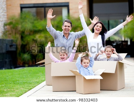 Happy family in cardboard boxes moving house - stock photo