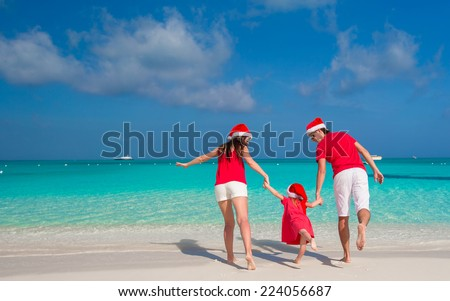 Happy family in Christmas Hats having fun on white beach - stock photo