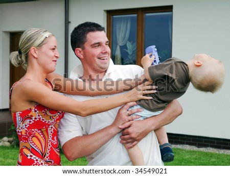 Happy family in front of their house - stock photo