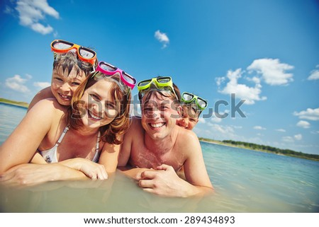 Happy family in goggles looking at camera in water - stock photo