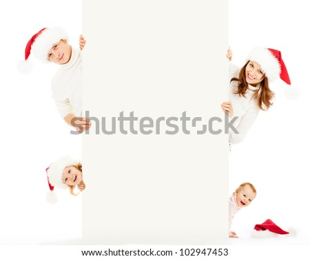 Happy family in Santa's hats with empty white banner for text isolated on white - stock photo