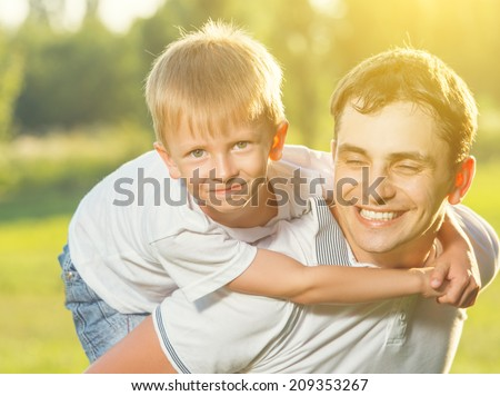happy family in summer nature. Dad and son hugging and laughing - stock photo