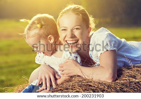 happy family in summer nature. Mother and baby daughter laugh, hug, play in the hay, straw. - stock photo