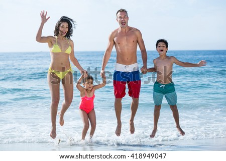 Happy family in swimwear holding hands while jumping at sea shore - stock photo