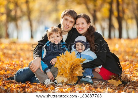 Happy family in the autumn park - stock photo