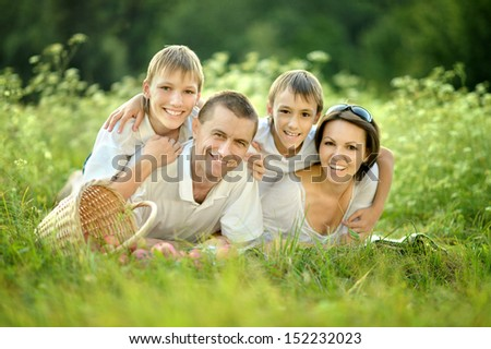 Happy family in the green summer park - stock photo