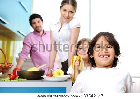 Happy family in the kitchen cooking dinner together - stock photo