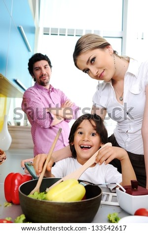 Happy family in the kitchen cooking dinner together and preparing food - stock photo