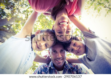 Happy family in the park huddling in circle on a sunny day - stock photo