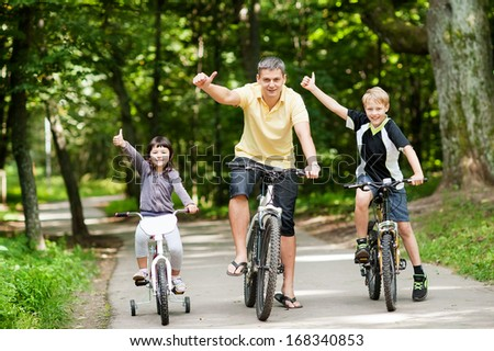 Happy family in the park on bicycles - stock photo