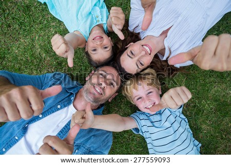 Happy family in the park together thumbs up on a sunny day - stock photo
