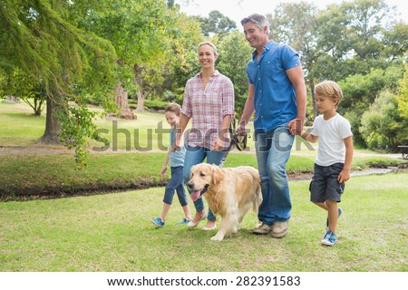 Happy family in the park with their dog on a sunny day - stock photo
