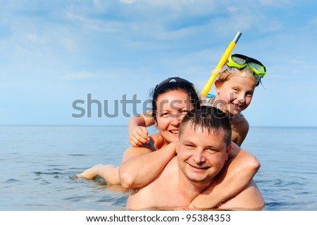 Happy family in the sea. Mum, the father and the daughter - stock photo