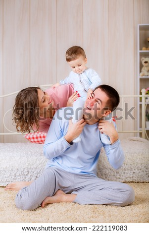 happy family in their pajamas on the bed in the nursery.  - stock photo
