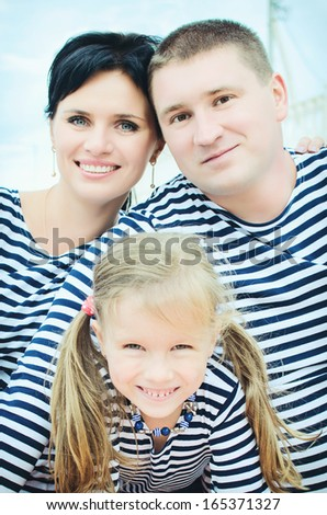 happy family in vests. beautiful mother, father and adorable daughter on beach in cold season. Smiling mum, dad and funny little daughter having fun at beach - stock photo