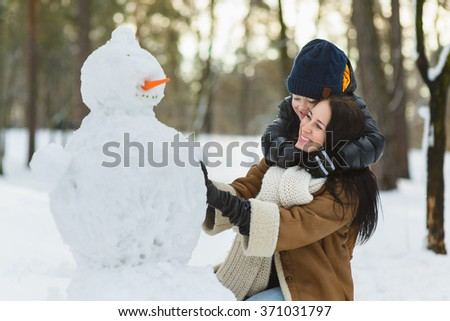 Happy family in warm clothing. Smiling mother and son making a snowman outdoor. The concept of winter activities - stock photo