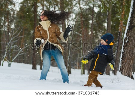 Happy family in warm clothing. Smiling mother and son play snowballs outdoor. The concept of winter activities - stock photo