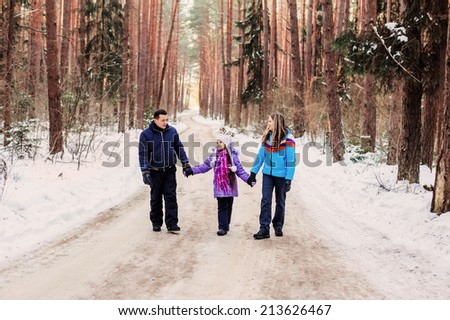 happy family in winter forest - stock photo