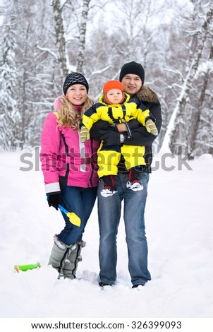 Happy family in winter forest full body portrait - stock photo