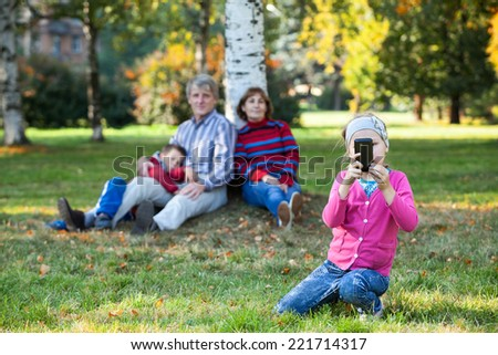 Happy family is on autumn park making pictures on phone - stock photo