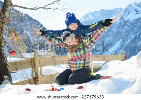 Happy family is playing airplane outside in a Alpine village - stock photo