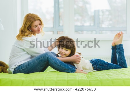 happy family. joyful contented mother stroking her daughter's hair - stock photo