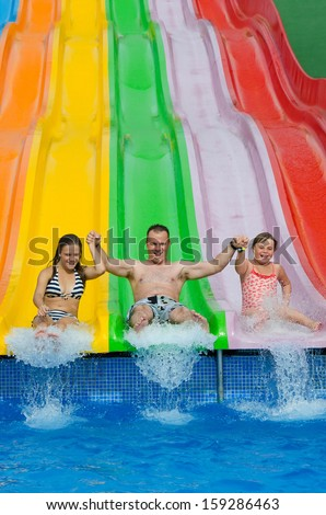 Happy family jump from the slide - stock photo