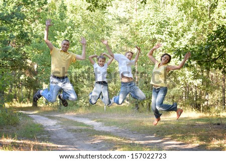 Happy family jumping in park - stock photo