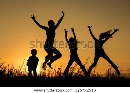 Happy family jumping in the park at the sunset time.  Concept of friendly family. - stock photo