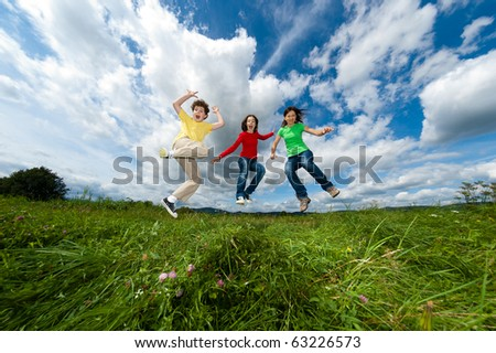 Happy family jumping, running outdoor - stock photo