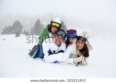 Happy family laying down in the snow - stock photo