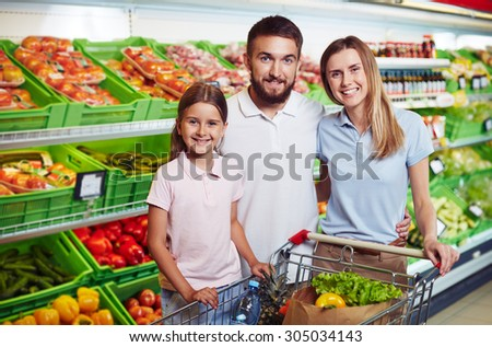 Happy family looking at camera in supermarket - stock photo