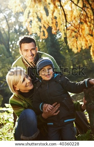 Happy family looking at camera, smiling outdoor in park at autumn. - stock photo